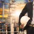 engineering man with white safety helmet standing in front of oil refinery building structure in heavy petrochemical industry