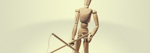 Freed from captivity puppet with rope in his hands on a light background. Concept on theme of freedom.