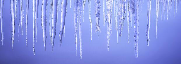 Eiszapfen hängen vom Dach beim Tauwetter