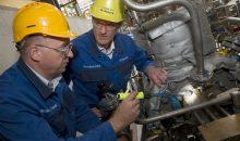 Zwei BASF-Mitarbeiter überprüfen in einer Produktionsanlage für Amine einen Sensor an einer Pumpe. (Bild: BASF)