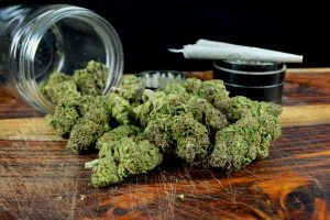 One ounce marijuana with jar, joints and grinder against black background