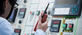 Industrial engineer working operated control panel with talking on the walkie-talkie for controlling work