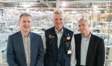 Igus-Geschäftsführer Frank Blase mit zwei Vertretern des Unternehmens Mura in einer Produktionshalle.