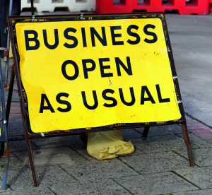 Yellow road sign stating business open as usual during period of