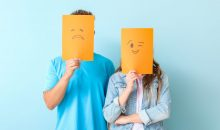 Young couple hiding faces behind emoticons against color background