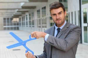 Businessman holding a giant pair of scissors