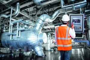 Maintenance engineer looking at monitor control in thermal power