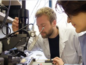 Sevda Abadpour (r.) und Axel Diewald vom Institut für Hochfrequenztechnik und Elektronik (IHE) des KIT positionieren einen Chip auf einer Platine. Gerade bei einer Größe im Mikrometerbereich muss alles perfekt ausgerichtet sein. (Bild: Joachim Hebeler, KIT)