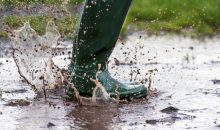 child jumping in a wet muddy puddle  with green wellington  boots  in the early morning light  copy space to side of image